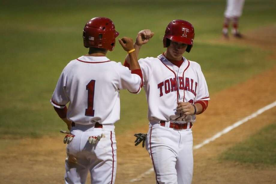Tomball's Josh Covey (1) and Joe Breaux (3) congratulate each other after both scored runs during the high school baseball game against Davis on Thursday, May 1, 2014, at Tomball High School. Photo: Michael Minasi