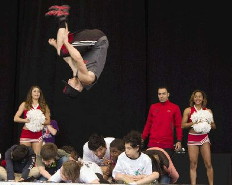 A member of the Houston Rockets Launch Crew flips over students during Musical Scores at The Cynthia Woods Mitchell Pavilion in The Woodlands Monday. More than 5,000 students and teachers from 33 different schools gather for the educational outreach program. The event was for academically at-risk students who earned the opportunity to attend the event by showing model behavior. Photo: Staff Photo By Ana Ramirez / The Conroe Courier/ The Woodland