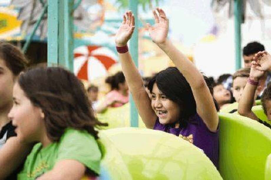 Abril Martinez, 8, throws her hands up on a ride during El Dia de la Familia Hispana on Sunday at the Montgomery County Fairgrounds.