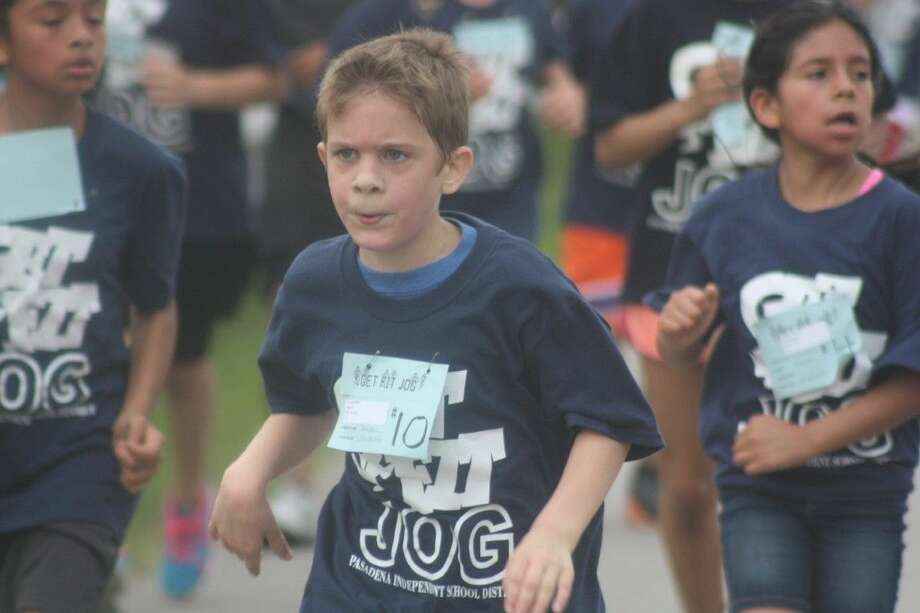 At about 9:10 a.m. next Saturday morning, the residential streets north of the football stadium will become bathed in Navy Blue Get Fit Jog T-shirts as the fifth graders hit the streets for the 2.3 mile excursion. This was a scene from last year's run down Dabney Street. Photo: Robert Avery