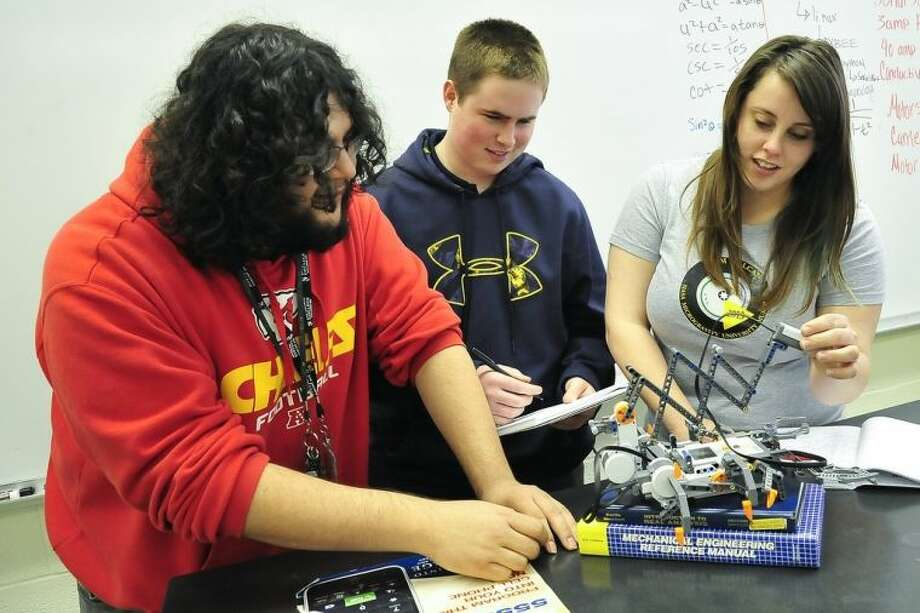 From left, San Jacinto College exemplary math students Miguel Rosales, Harrison Mast and Darby Macha participated in Tech Friday learning exercises. The three are shown working on a robotics device at the College's robotics lab. Photo credit: Rob Vanya, San Jacinto College marketing, public relations, and government affairs department.