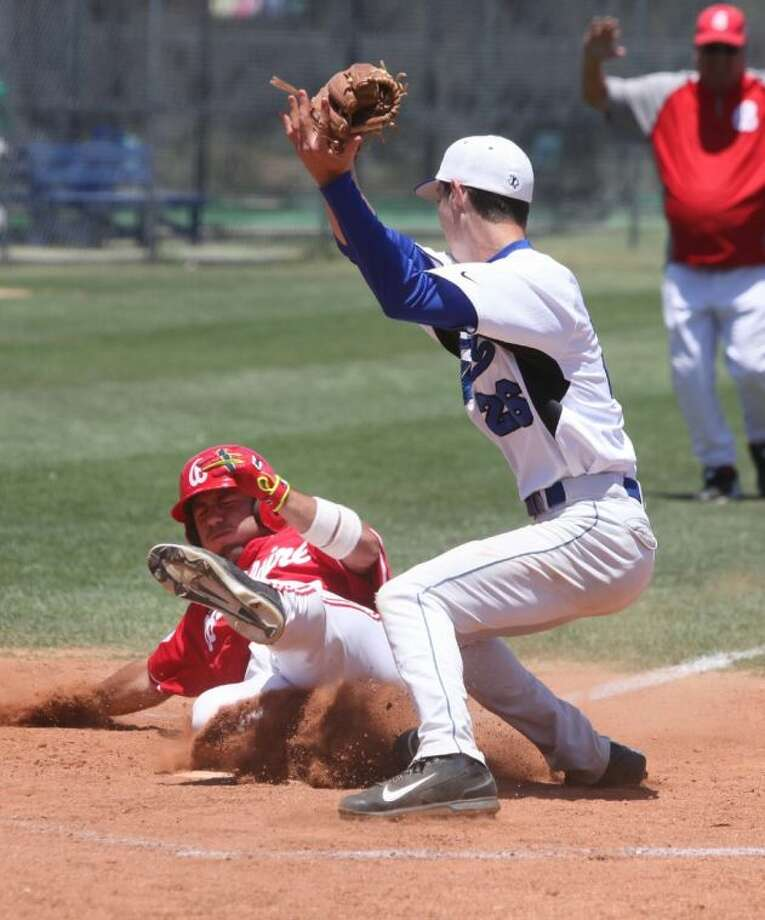 Bellaire's Ethan Clasen slides across the pate while Katy Taylor's Tanner Knowles takes the throw but can't make a tag at home plate during the teams' Bi District basebal state playoffs Saturday afternoon in Katy. Taylor won Game Three in the best-of-three series to win and advance to this week's 5A Area Round against Cy Creek. . Photo: Alan Warren