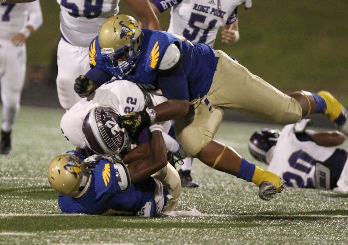 Elkins' Ross Blacklock and Kadari Adams bring down Ridge Point's Remus Bulmer during their district game Oct. 16 at Hall Stadium in Missouri City. To view or purchase this photo and others like it, go to HCNPics.com.