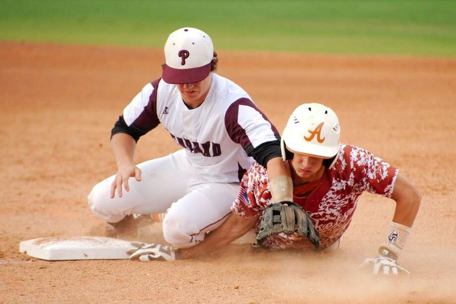 Pearland's Ben Paddock (5) struggles to hold onto the ball as Alvin's Nathan Collins (2) dives into first base Monday.