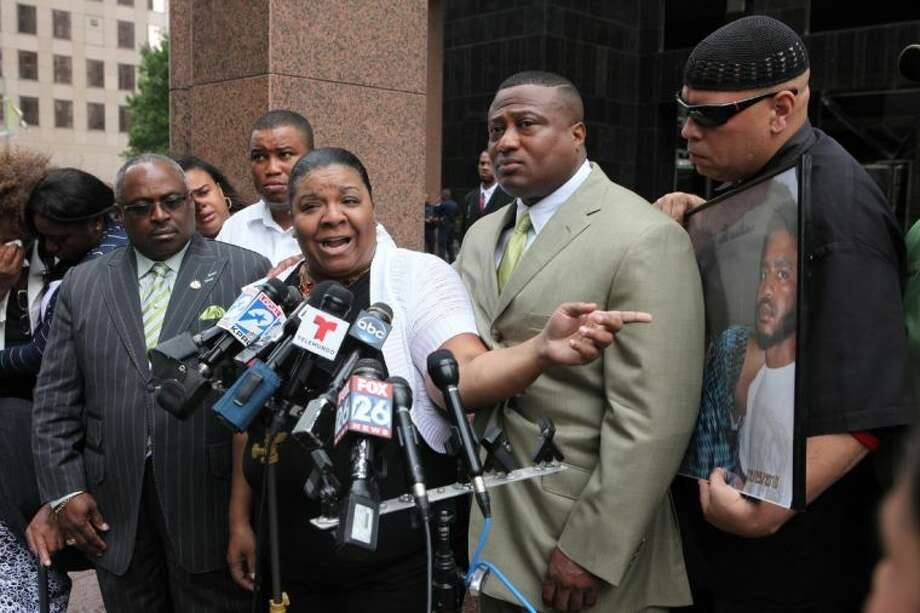 Kimberly Blair-Olaniyi, mother of the victim, 26-year old Michael Garrett Blair, talks about the fatal police shooting and secret videotape with Quanell X and other family members Wednesday during a press conference in front of the Federal Department of Justice Building. Photo: Alan Warren