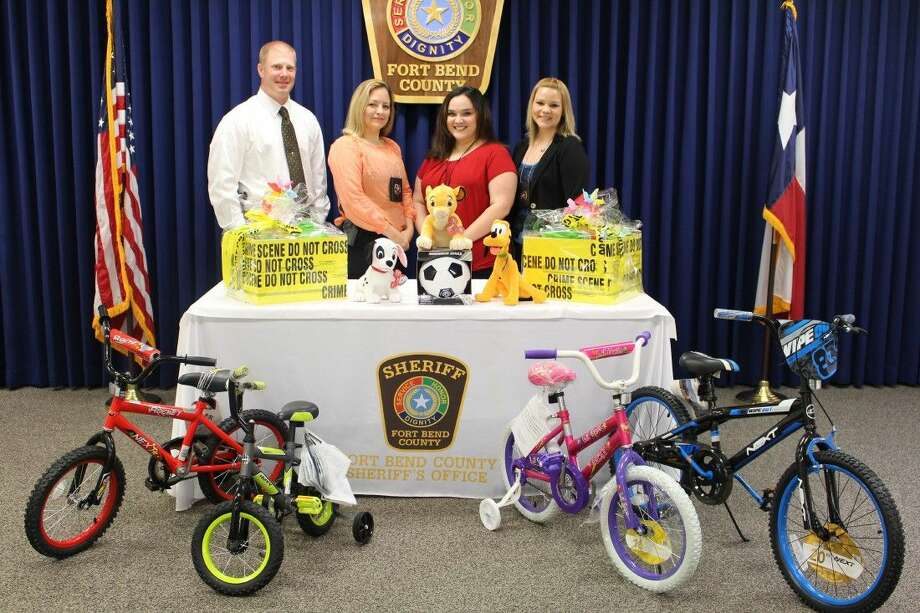 Members of the Fort Bend County Sheriff's Office Crimes Against Children and Elderly are shown with some of the raffle itmes for the 2015 Pinwheel Project. From left, Sgt. Jarret Nethery and detectives Susan Hobbs, Julie Delgado and Lesley Vaught