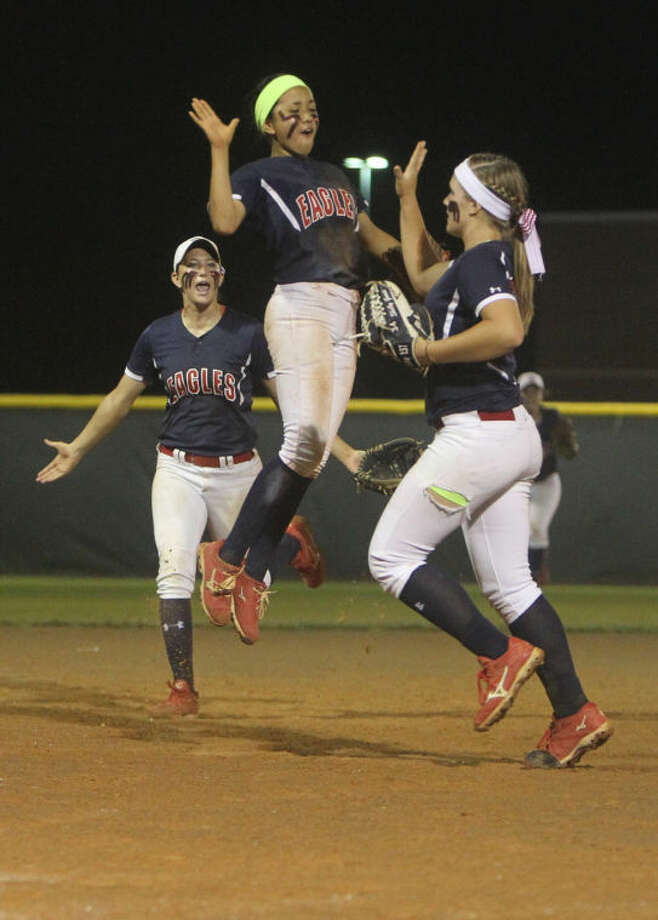 Atascocita's Sarah Cedillo celebrates with pitcher Shelby McGlaun (34) after strking out The Woodlands' Brittany Mann (5) with two runners on base to end the top of the seventh inning during Game 1 of a regional quarterfinal series at Porter High School Friday. Photo: Jason Fochtman