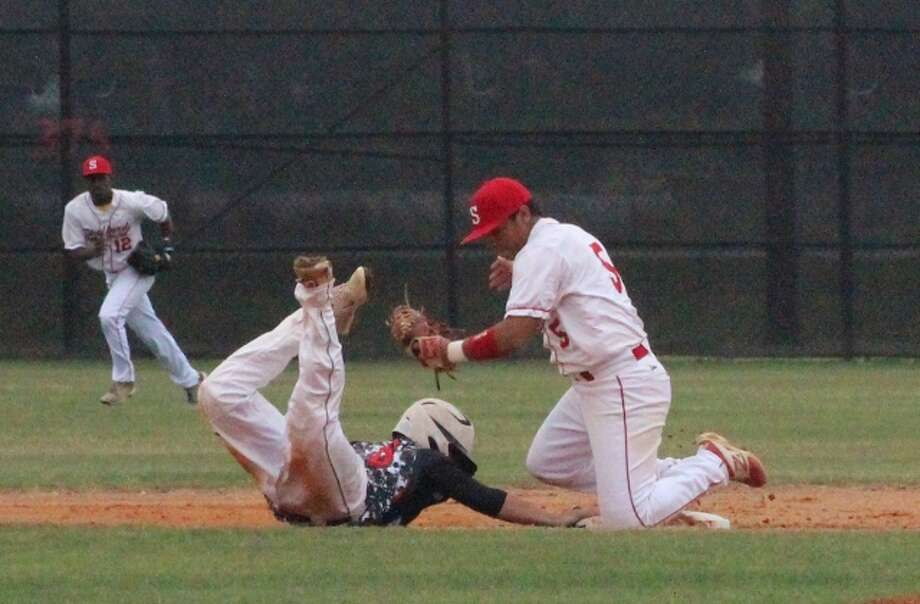 Falcons' left-fielder Clay Barnes dives back into second base on a pickoff play during third inning action against the Stafford Spartans.  Barnes later scored helping Huffman advance to the regional quarterfinals with a 3-2 win. Photo: Louis Roesch