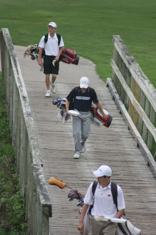 Deer Park's Cort Crawley (top) walks the bridge to one of the extra holes during the first day of the Region III tournament. In front of him is a Houston Memorial player and in the middle is Clear Lake's Nate Zahn. The Falcons also clinched a state title meet berth. Photo: Robert Avery