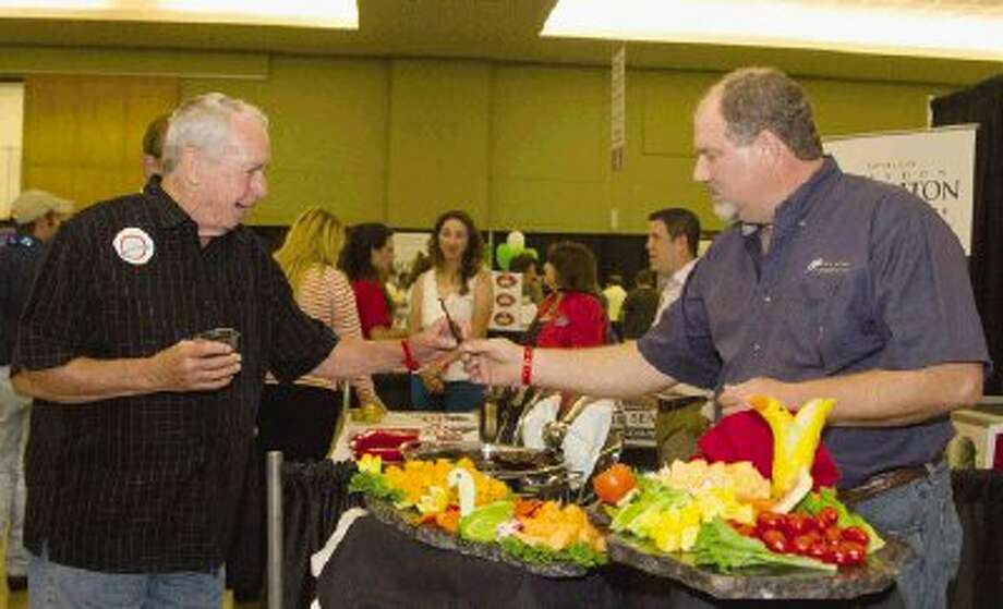 Jack Hardie is handed candied bacon from the owner of All Star Catering, Don Spence, during this year's Tastefest at the Lone Star Convention and Expo Center in Conroe on Thursday. The event allows the community to sample items from local restaurants. Photo: Staff Photo By Ana Ramirez / The Conroe Courier