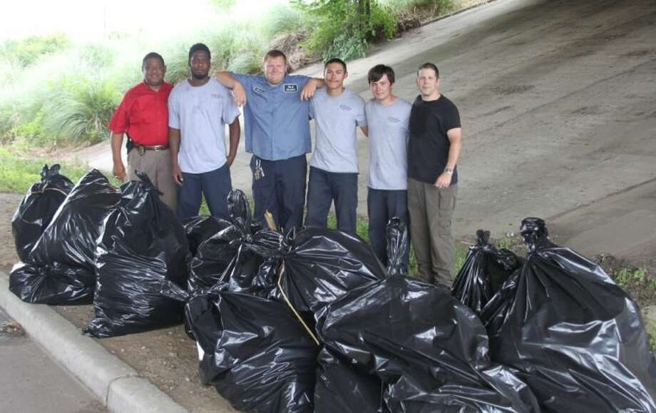 Employees working for the City of Cleveland's public works department and police department stand next to the 16 large trash bags of garbage that was picked up from under the overpass of US 59 at SH 105. Pictured left to right are Cleveland Police Chief Darrel Broussard; Public Works employees, Kavin Harrell, Cameron Edwards, Micah McAdams and Joshua Knox; and Cleveland Police Capt. Scott Felts. Photo: VANESA BRASHIER