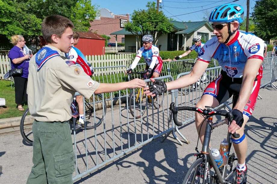 """When arriving at the historic Tomball depot, Ride 2 Recovery cyclists received a specially designed """"challenge coin"""" from Eagle Scouts representing Troop 471. Photo: Submitted"""