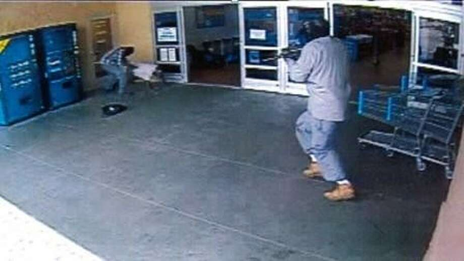 Pearland Police released security camera images from an armored car robbery that occured outside the Wal-Mart located at 1919 N. Main Friday (May9). The first image depicts one suspect ordering the guard to the ground while the other suspect points a long gun at him Photo: Courtesy Pearland Police Dept.