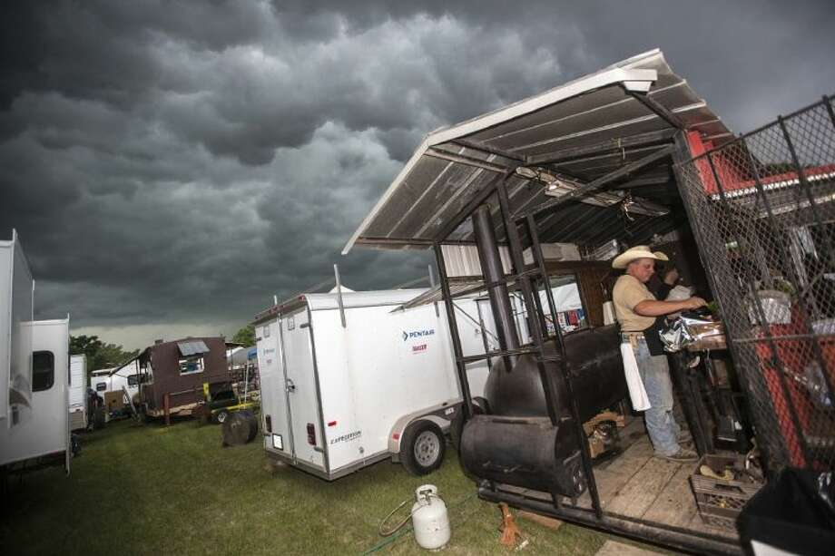 Brandy McShan seasons a rack of ribs as storm clouds roll through Northeast Houston during the Founder's Day festivities May 9, 2014, at Splendora City Park. Photo: ANDREW BUCKLEY