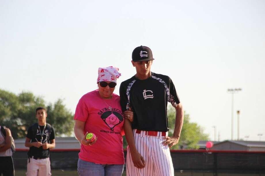 "Langham Creek High School parent Brenda Vasquez is escorted onto the field to throw her pitch in ""Pitches in Memory"" by her son, Langham Creek baseball player Alejandro Vasquez. (Photo by Robert Jordan, Langham Creek HS)"
