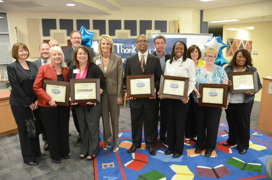 Representatives from the Region IV Education Service Center, Greater True Faith Missionary Baptist Church, Caterpillar and Caldwell Companies display their certificates of adoption from the Adopt-a-School ceremony at Holbrook on April 21.