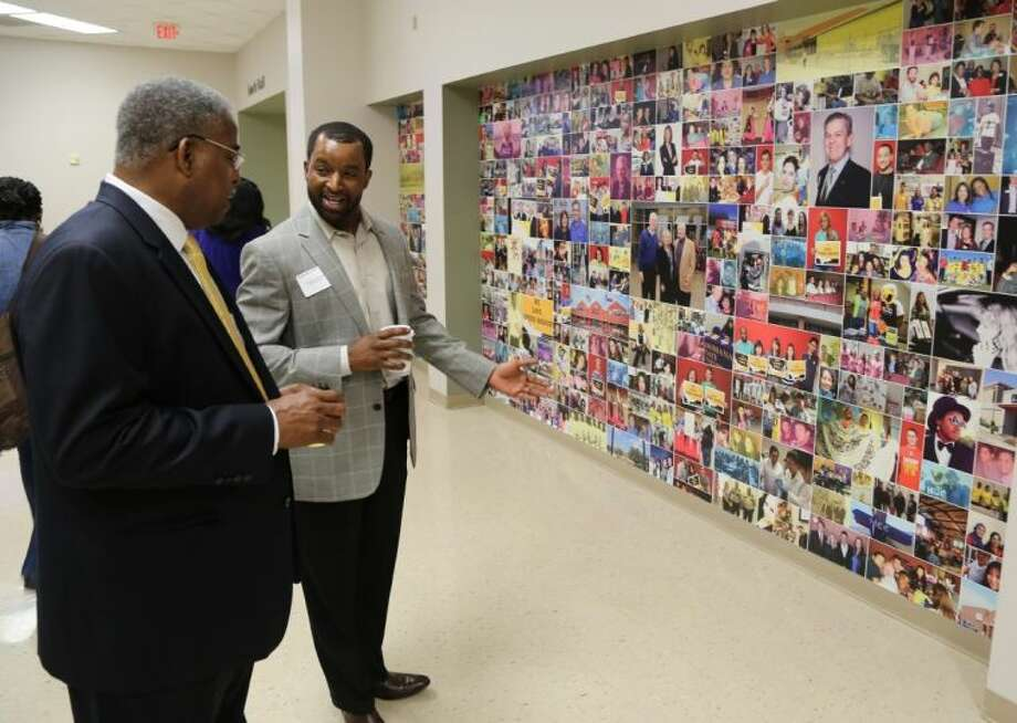 Checking out the photo wall last week at HCC Spring Branch are Robert Harris (left), advising manager and DeRodrick Jonkins, financial aid officer. Photo: Rusty Graham