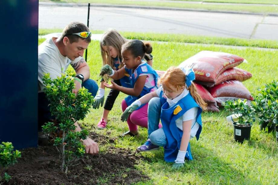 Calpine Industries volunteer Joshua Hendrick is assisted by Parkwood Elementary Girl Scout Daisies Toni Beth, Kayden McClendon and Avery Gustke as they prepare a bed for planting shrubs on the school ground for Earth Day Wednesday, April 22.