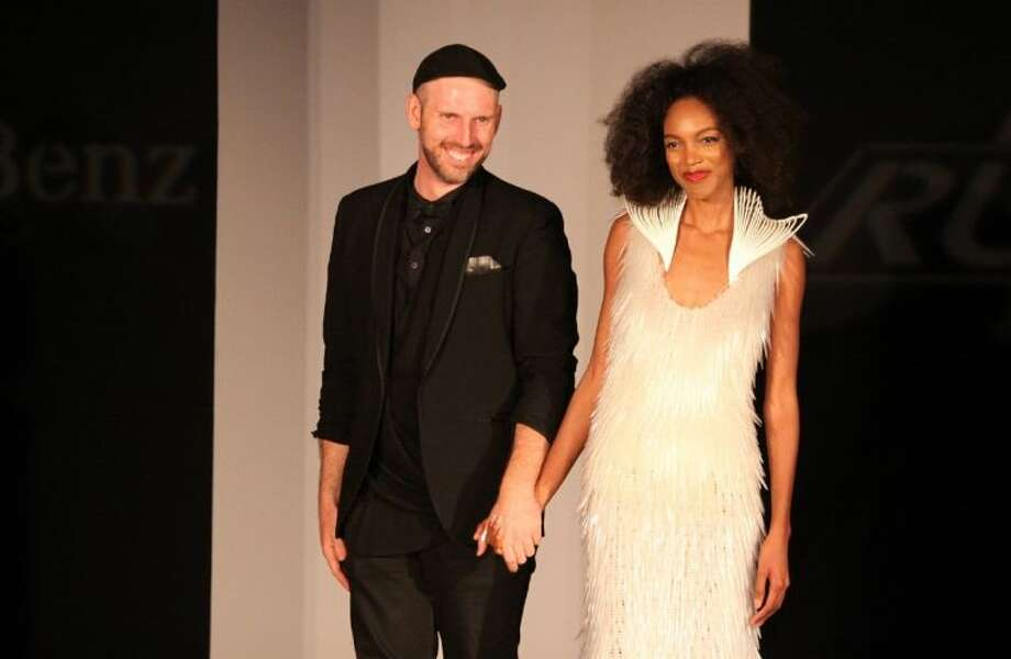 Project Runway finalist Justin LeBlanc with a model wearing his dress design at the fashion show at Mercedes-Benz of Sugar Land on Thursday evening, May 8. Photo: Alan Warren
