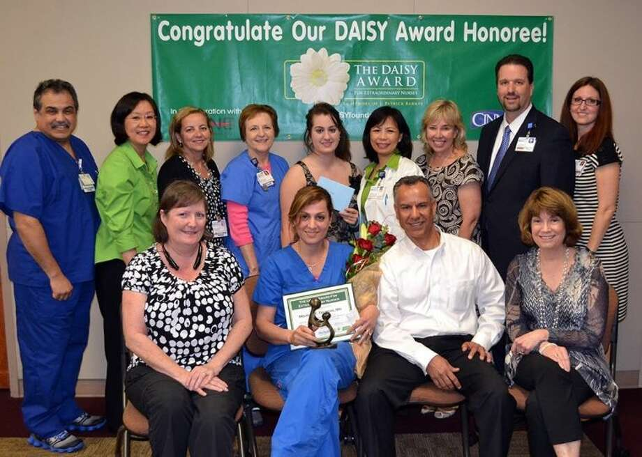 DAISY Award recipient Mojgan Tourchi, RN, with family, the nominating patients and the DAISY Award Committee. Photo: Houston Methodist Sugar Land