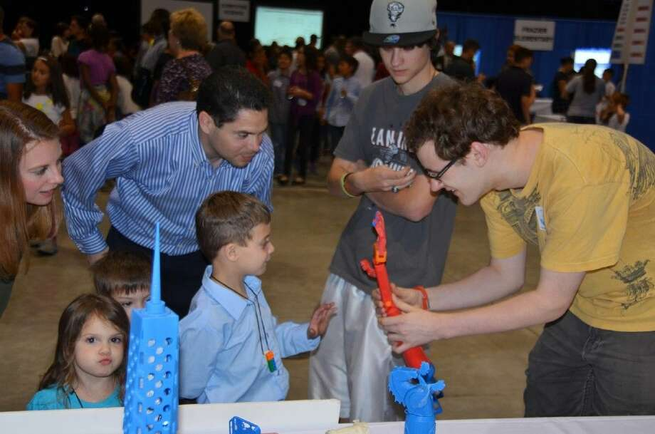 Cy-Fair High School advanced engineering design student Andrew Vallhonrat shows a 3D hand model he created with a 3D printer to Technology Festival visitors in May 2014. Recently certified in Autodesk Inventor Professional, Vallhonrat created the model in the Cy-Fair High School lab.