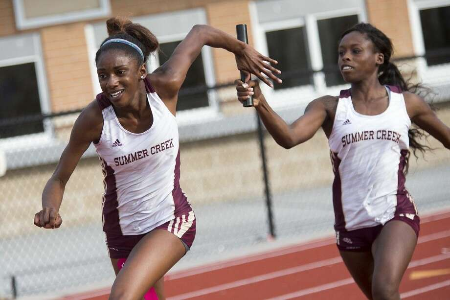 Summer Creek's Bryanah Rideaux receives the batton from Danae Daron during the District 15/16 Area Track Championship on April 23, 2015, at Turner Stadium in Humble. Photo: ANDREW BUCKLEY