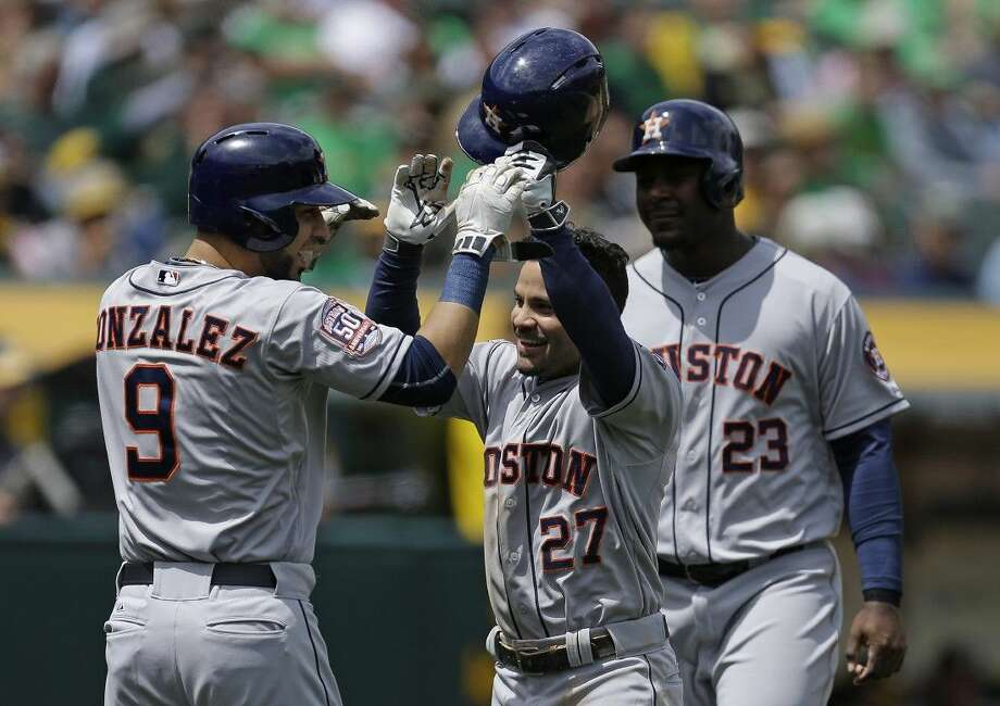 Houston Astros' Jose Altuve celebrates with Marwin Gonzalez and Chris Carter, right, after Altuve hit a three run home run Saturday in Oakland, Calif.