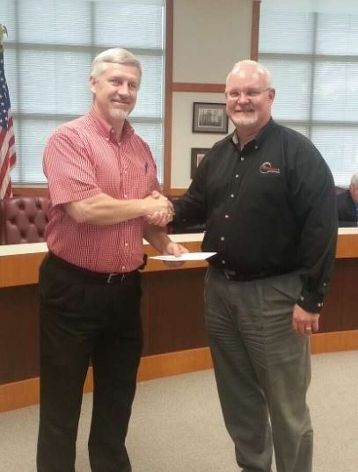 Cleveland ISD Board President Chris Wood (left) thanks Ted Wiggins, chief financial officer of Performance Trucking Company, for the donation of $18,725 that will be used to replace two stolen HVAC systems. Photo: Submitted