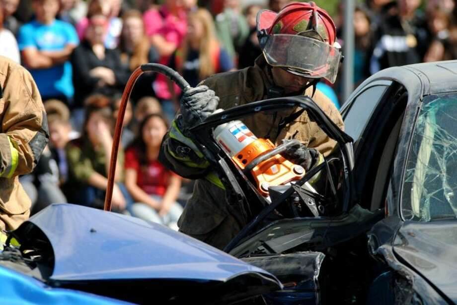 A member of the Manvel Volunteer Fire Department works to pull a student from the wrecked car. Photo by: Karla Leyja