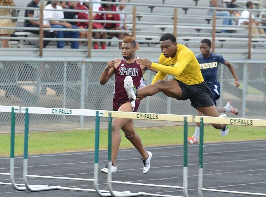 Cypress Falls junior Isaiah Lucas vaults a hurdle with Cy-Fair junior Caleb Richmond and Cypress Ranch sophomore Sean Marshall behind him in the 300-meter hurdles event at the Area Track and Field Meet. Lucas won the event, with Richmond second and Marshall third.