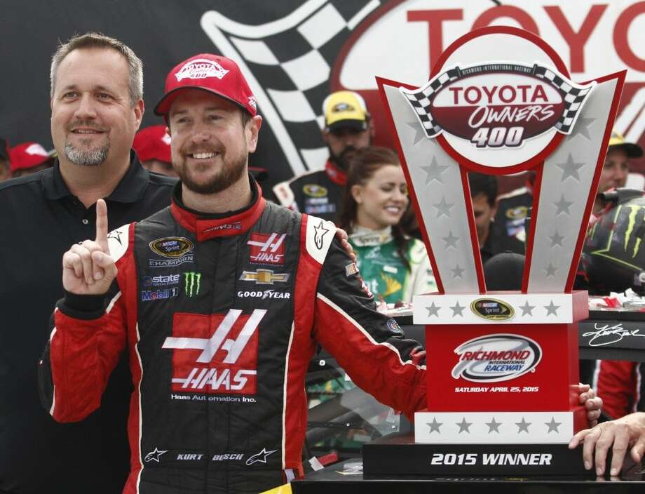 Kurt Busch, second from left, stands with the trophy after winning the NASCAR Sprint Cup auto race at Richmond International Raceway.