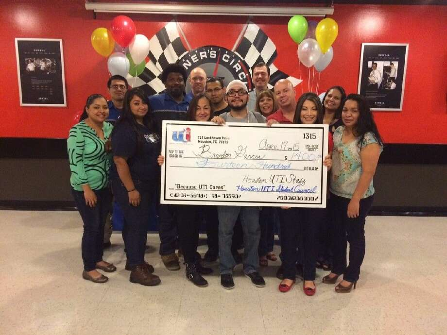 Universal Technical Institute alumus Brandon Garcia, 24, receives a surprise $1,400 check from staff and students from UTI's Houston campus to help with medical expenses as he fights grade four brain cancer.