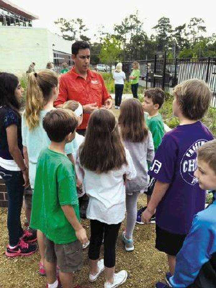 Jaime Gonzalez from the Katy Prairie Conservancy talks to Frostwood students before they plant the San Jacinto Battleground bee balm in their pocket prairie.