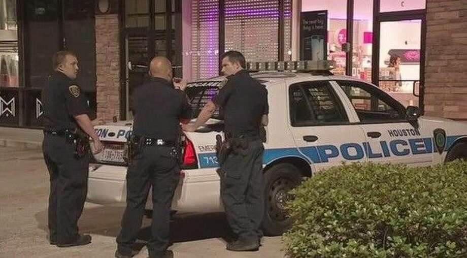 Houston Police officers work to investigate an aggravated robbery at the T-Mobile store in the 2500 block of Green Oak in Kingwood Monday, April 27, 2015.