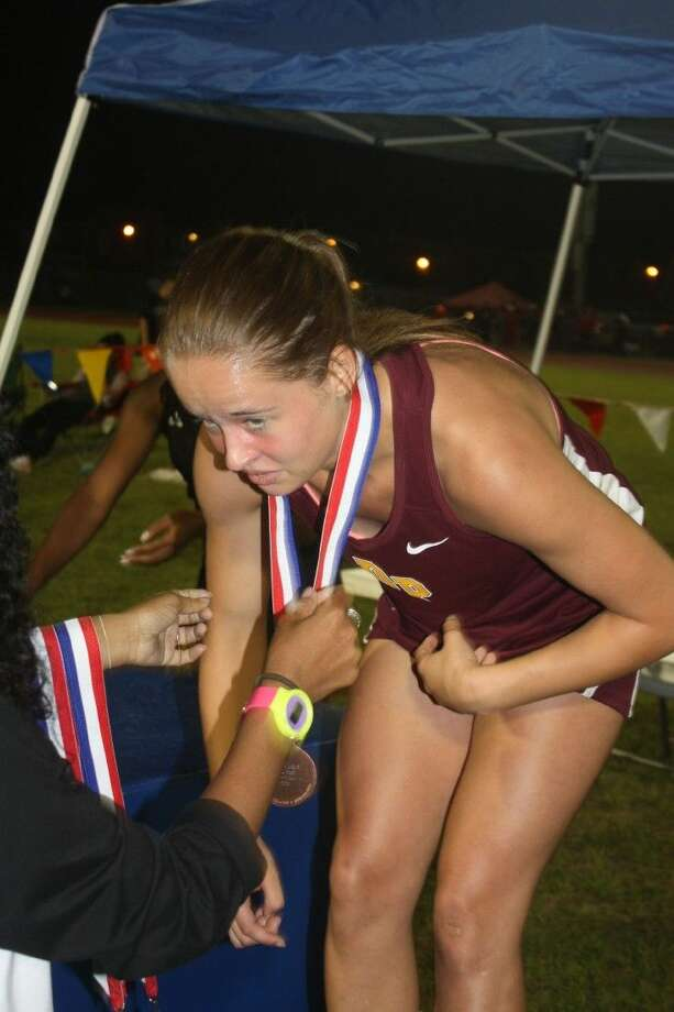 Freshman Emily West has a medal placed around her neck on the medals stand during last Thursday's Area meet, following her 25-second run in the 200-meters. This weekend, she competes at the Region III meet. Photo: Robert Avery