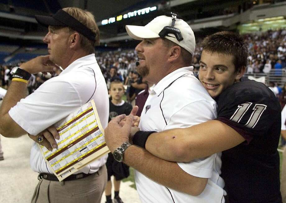 Mike Norman is hugged by Pearland quarterback Trey Anderson during the Oilers' 2010 state semifinal win over San Antonio Stevens in the Alamodome. Norman has been hired as Pasadena Dobie's new head football coach. At left, is Oiler head coach Tony Heath. Photo: FILE PHOTO