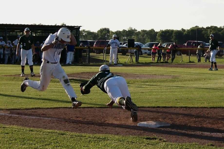 Hardin's Taylor Thompson makes first when East Chambers first baseman Johnny Trent makes a dive for the throw in the bottom of the sixth, April 29, 2015