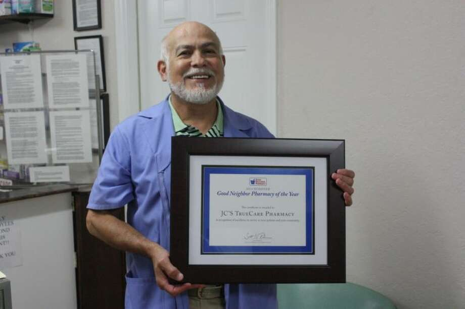 Juan Cantu displays the award given to J.C.'s Pharmacy for its nomination as Pharmacy of the Year. Photo: JACOB MCADAMS
