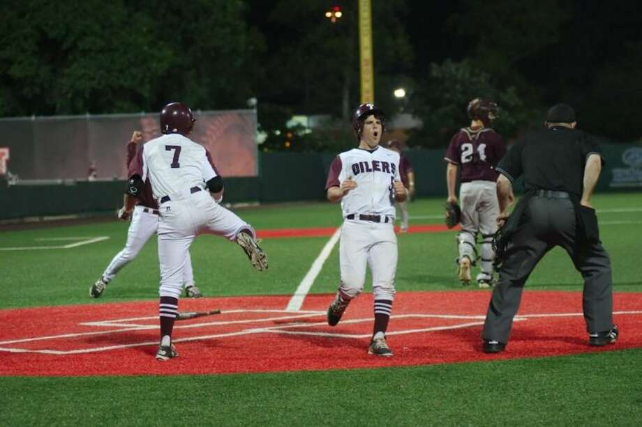 Pearland's Kamren Dukes (7) celebrates as Ben Paddock (5) crosses home plate with the game-winning run in the bottom of the ninth inning Thursday in the first game of the teams' best-of-three series. Photo: KIRK SIDES