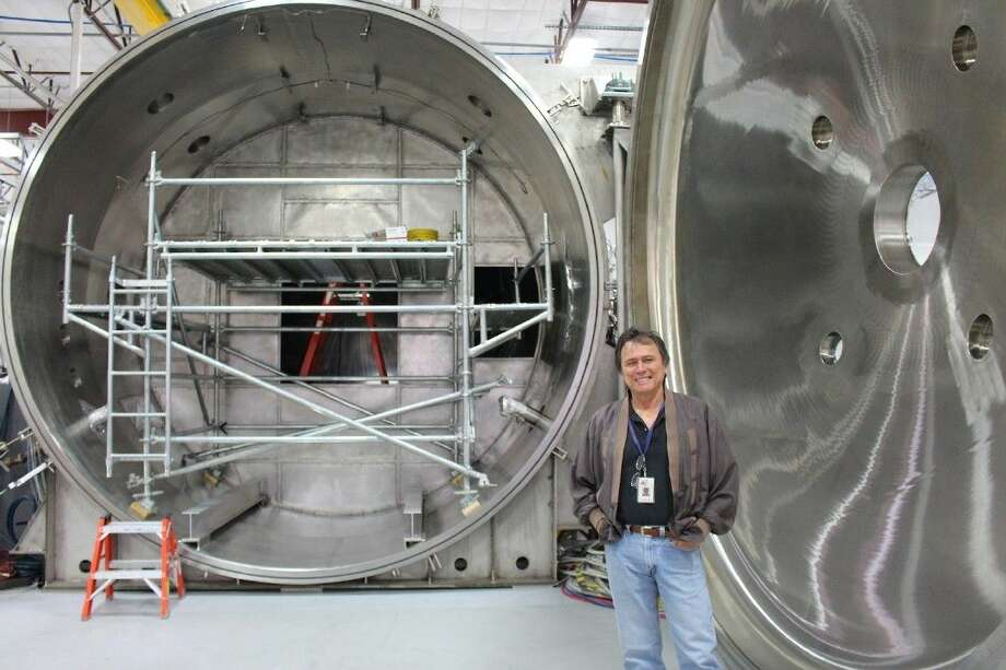 Dr. Franklin Chang-Diaz stands in front of the test vacuum chamber in Ad Astra's Clear Lake warehouse.
