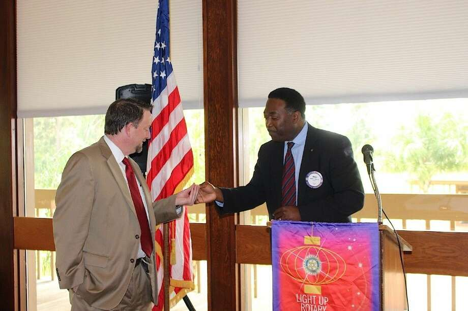 New Rotarian Mark Smith receives his pin from President Noble Alix.