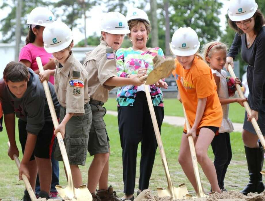 Principal Nancy Harn leans out of the way as Rummel Creek students turn dirt Tuesday at the groundbreaking ceremony. Photo: Rusty Graham