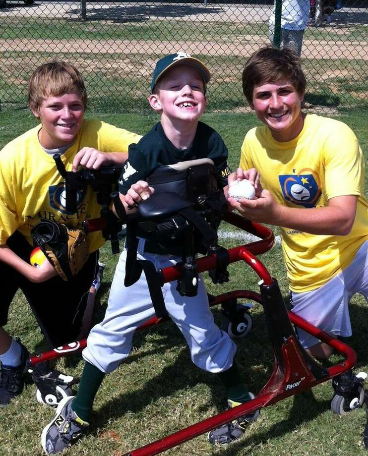 Miracle League A's player Reece Simmons, a Hamilton Elementary School fourth-grade student; and Buddies Logan Wallace, left, Cypress Ranch High School senior; and Mikey Hoehner, right, Langham Creek High School junior, enjoy a Saturday at the Langham Creek Family YMCA ballpark serving children with special needs. The new Adaptive Sports Complex will be the official Houston home of the Miracle League. Photo: Courtesy Of CFISD