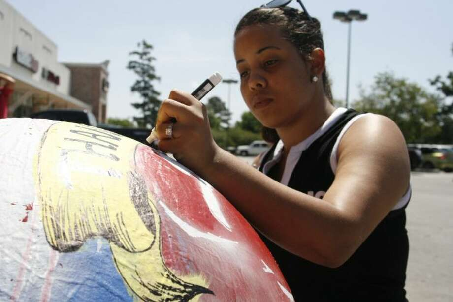 H-E-B employee Toni Kruppenbacher paints the globes outside of the H-E-B in Atascocita with patriotic images such as the flag, a soldier, the Statue of Liberty and fireworks Saturday, May 17, 2014.