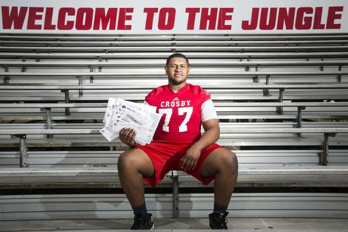 Cougars offensive lineman Keenan Murphy poses for a portrait with a portion of his collection of letters from universities across the country showing interest in his football abilities March 10, 2015, at Crosby High School.