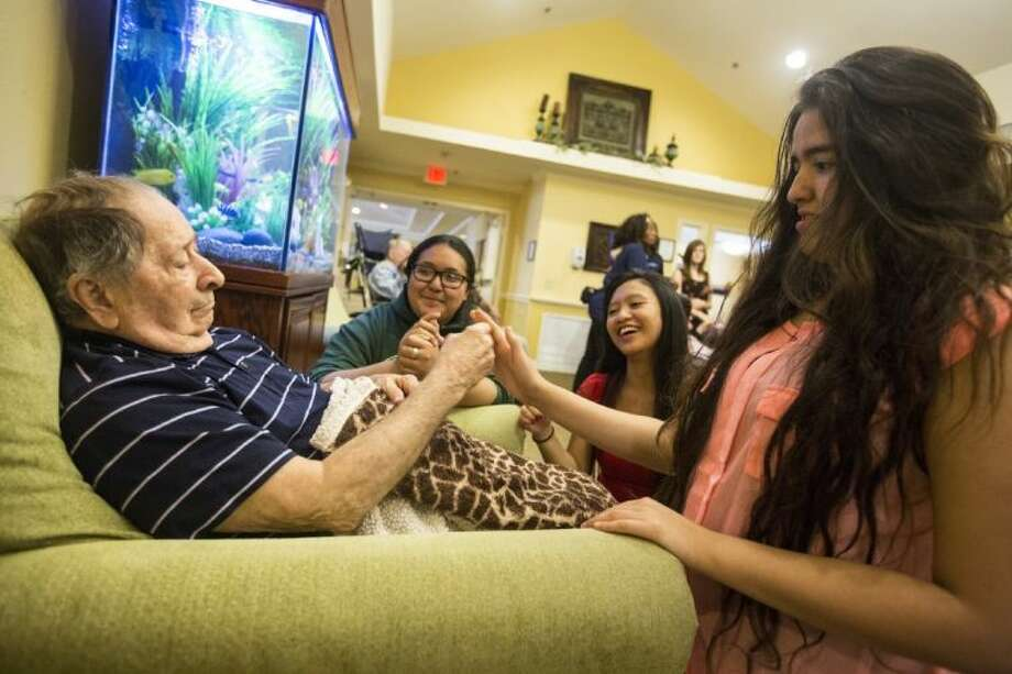 FROM RIGHT: Quest students Alejandra Cortes, Ginella Burra and Victoria Garcia visit with Silverado resident David Frawley during a graduation celebration for Quest Early College High School students on May 30, 2014, at Silverado's Kingwood Memory Care Community. The students in the program have given their time over the past two to three years to gain experience and connect with the residents who suffer from various types of dementia. Photo: ANDREW BUCKLEY