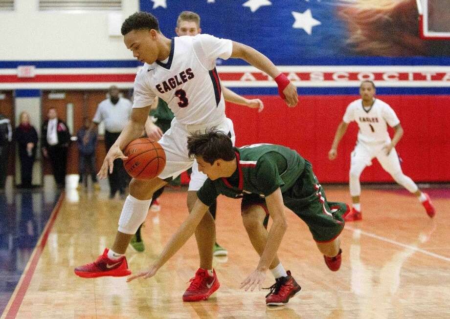 Atascocita point guard Carsen Edwards stips the ball away from The Woodlands guard Clay Creighton during the first quarter of a basketball game at Atascocita High School Tuesday.