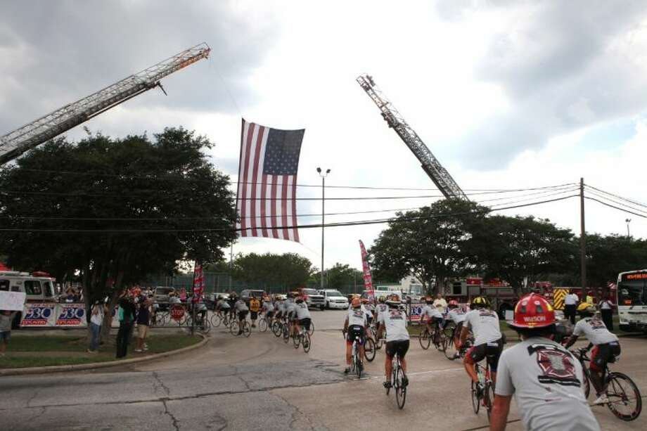 The Brotherhood Ride goes under a American flag held by ladders from HFD stations 51 and 68 off Gessner into HFD Station 68. Photo: Alan Warren