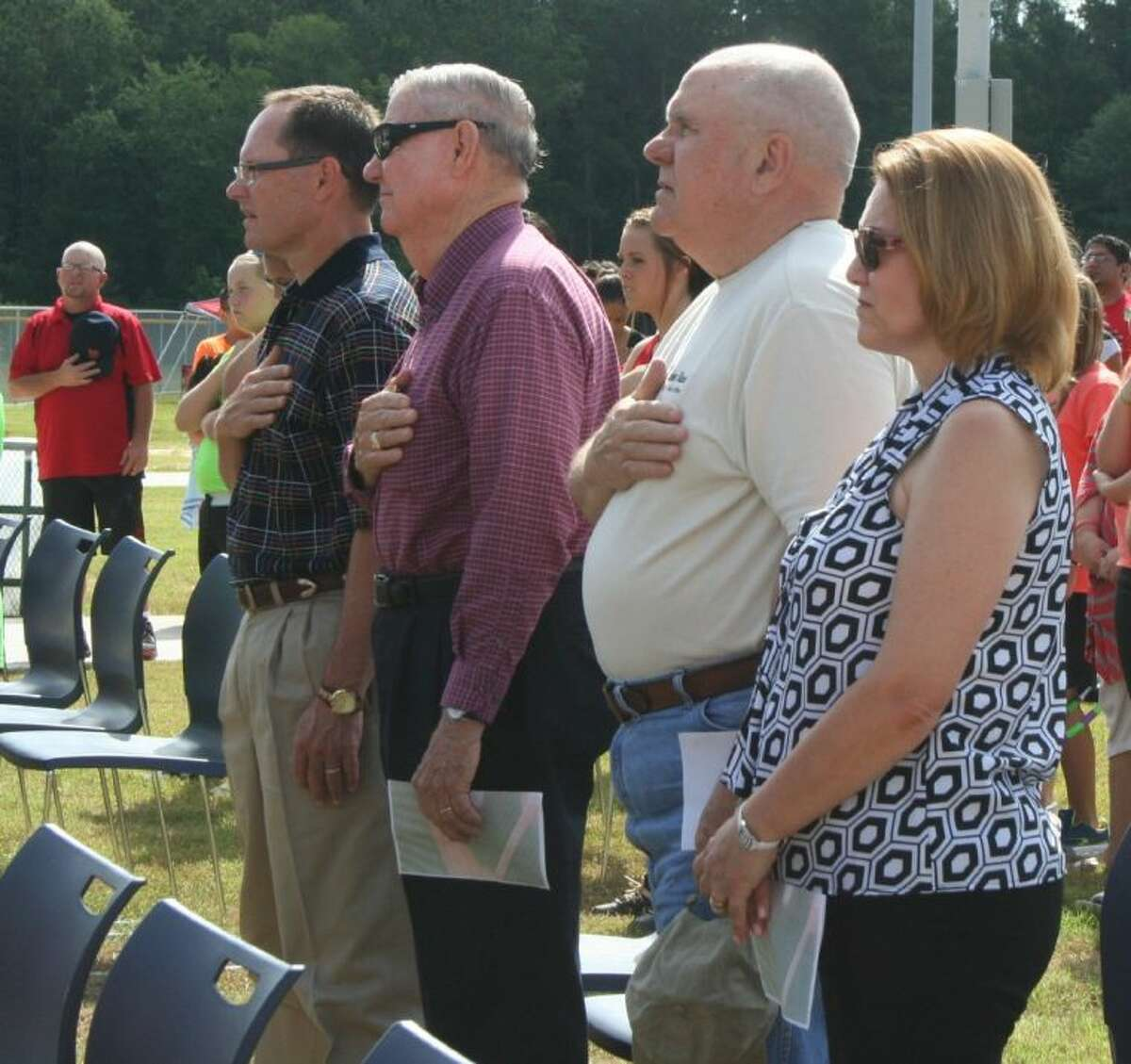 Cleveland community members hold their hands over their hearts as they listen to the singing of the national anthem during the opening ceremony for Cleveland Municipal Park.
