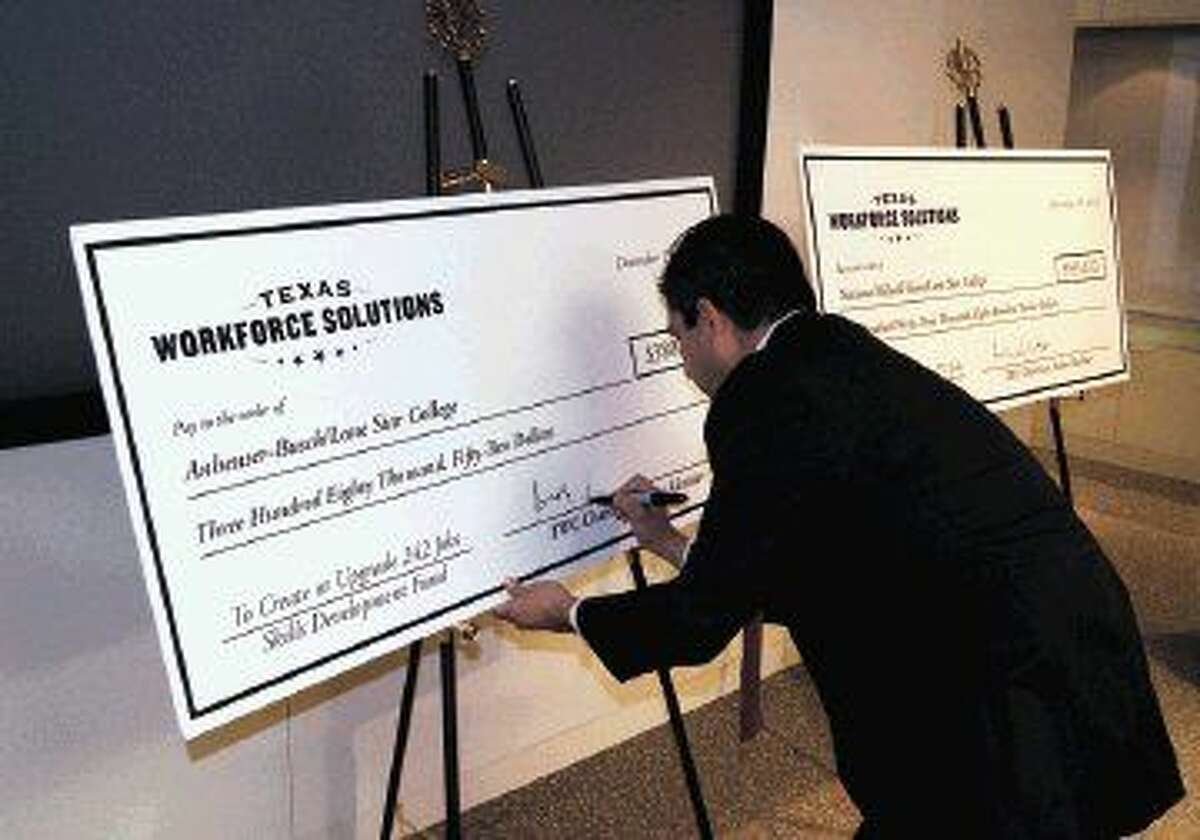 TWC chairman Andres Alcantar signs checks for the $913,865 Skills Development Fund grants given to Lone Star College by Texas Workforce Solutions to help train current and new employees at National Oilwell Varco and Anheuser-Busch.